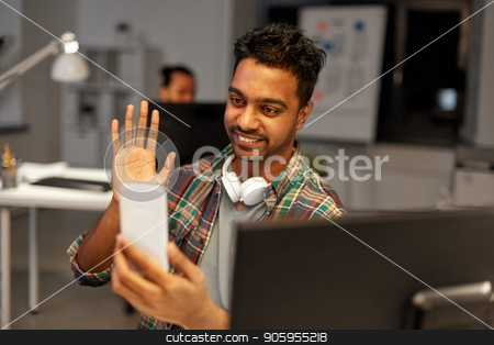 man with smartphone having video call at office stock photo, technology, communication and deadline concept - creative man with smartphone having video call at night office and waving hand by Syda Productions
