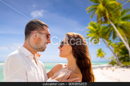 happy couple in sunglasses over tropical beach stock photo, travel, tourism and summer vacation concept - happy smiling couple in sunglasses hugging over tropical beach background in french polynesia by Syda Productions