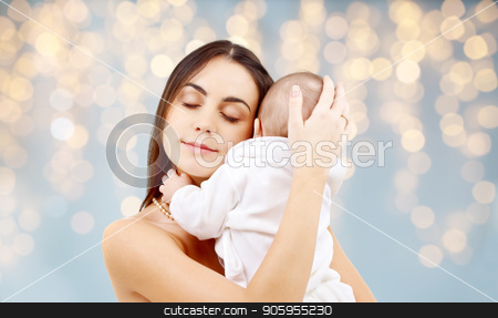mother with baby over festive lights background stock photo, family and motherhood concept - happy smiling young mother with little baby over festive lights background by Syda Productions