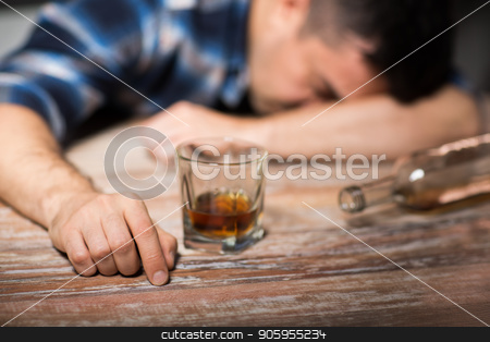 drunk man with glass of alcohol on table at night stock photo, alcoholism, alcohol addiction and people concept - male alcoholic with glass of whiskey and bottle lying or sleeping on table at night by Syda Productions