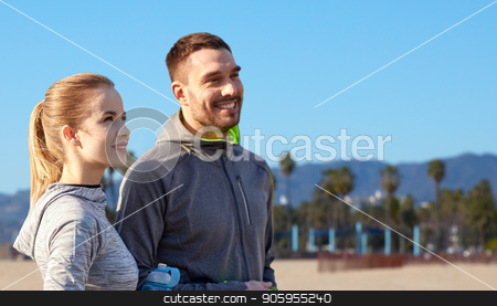 couple of sportsmen with water over venice beach stock photo, fitness, sport and people concept - smiling couple with bottles of water over venice beach background in california by Syda Productions