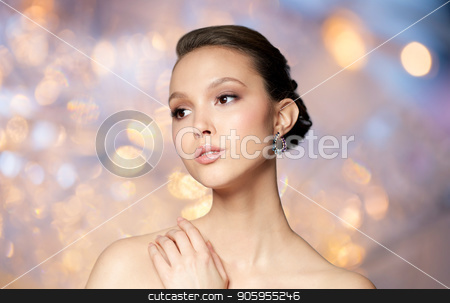 close up of beautiful woman face with earring stock photo, beauty, jewelry, accessories, people and luxury concept - close up of beautiful asian woman face with earring over holidays lights background by Syda Productions