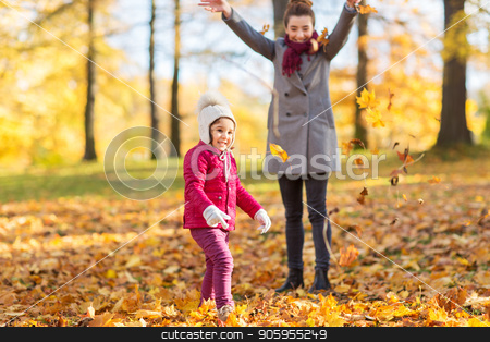 happy family playing with autumn leaves at park stock photo, family, season and people concept - happy mother and little daughter playing with autumn leaves at park by Syda Productions
