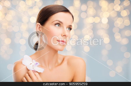 woman with orchid flower over green background stock photo, wellness and beauty concept - beautiful bare woman with orchid flower over holidays lights background by Syda Productions