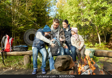 family with backpacks and thermos at campfire stock photo, camping, tourism and family concept - happy mother, father, son and daughter with backpacks and thermos at camp fire in woods by Syda Productions