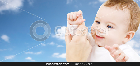 close up of sweet little baby with mother hand stock photo, family, childhood and people concept - close up of sweet little baby with mother hand over sky background by Syda Productions