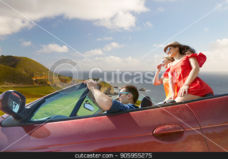 friends driving in convertible car over big sur stock photo, summer holidays, road trip and travel concept - happy friends driving in convertible car over big sur coast of california background by Syda Productions
