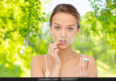young woman applying lip balm to her lips stock photo, beauty, people and cosmetics concept - young woman applying lip balm over green natural background by Syda Productions
