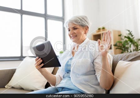 senior woman having video chat on tablet pc stock photo, technology, people and communication concept - happy senior woman with tablet pc computer having video chat at home by Syda Productions