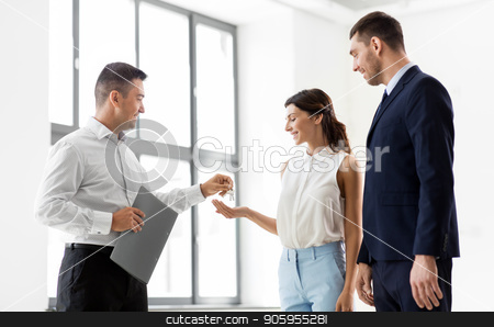 realtor giving key to customers at new office stock photo, real estate business, sale and people concept - realtor giving key to customers or new office owner by Syda Productions