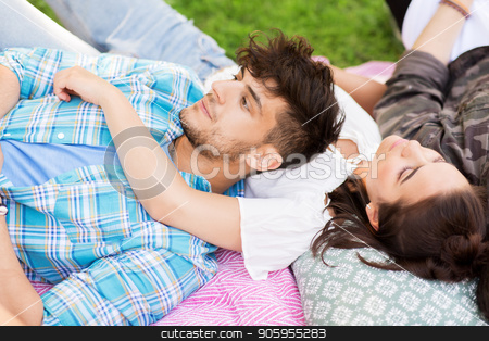 happy friends chilling on picnic blanket at summer stock photo, friendship, leisure and summer concept - group of happy friends chilling on picnic blanket at park by Syda Productions