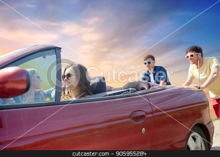 friends pushing broken convertible car stock photo, leisure, road trip, travel and people concept - friends pushing broken convertible car over sky background by Syda Productions