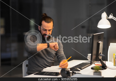 man with smartwatch using voice recorder at office stock photo, deadline, technology and people concept - creative man with smartwatch using voice command recorder and working late at night office by Syda Productions