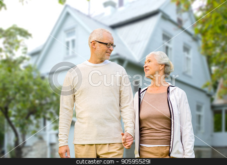 happy senior couple holding hands over house stock photo, old age, accommodation and real estate concept - happy senior couple holding hands over living house background by Syda Productions