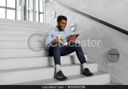 businessman with tablet pc and coffee on stairs stock photo, business, people and technology concept - african american businessman with tablet pc computer drinking coffee at office stairs by Syda Productions