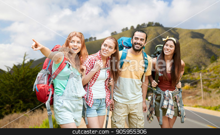group of friends with backpacks over big sur hills stock photo, adventure, travel, tourism, hike and people concept - group of smiling friends with backpacks pointing finger over big sur hills of california background by Syda Productions