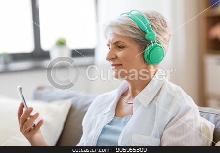 senior woman in headphones listening to music stock photo, technology, people and lifestyle concept - happy senior woman in headphones and smartphone listening to music at home by Syda Productions