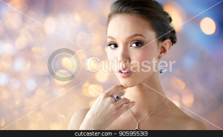 beautiful woman with earring, ring and pendant stock photo, beauty, jewelry, people and luxury concept - beautiful asian woman or bride with earring, finger ring and pendant over holidays lights background by Syda Productions