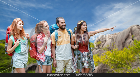 friends with backpacks over seychelles island  stock photo, travel, tourism, hike and adventure concept - group of smiling friends with backpacks pointing finger to something over background of seychelles island by Syda Productions