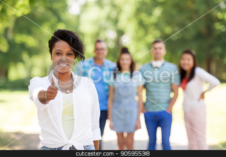 group of happy international friends outdoors stock photo, people, friendship and international concept - happy smiling woman showing thumbs up and group of happy friends outdoors by Syda Productions
