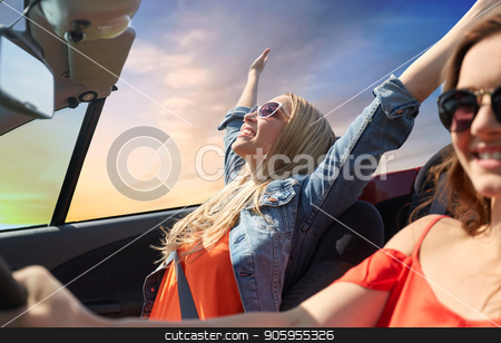 happy young women driving in convertible car stock photo, summer holidays, road trip, vacation, travel and people concept - happy young women driving in convertible car and laughing over sky background by Syda Productions