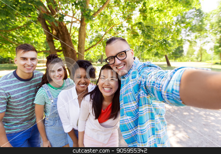 group of happy international friends taking selfie stock photo, people, friendship and international concept - happy smiling young woman and group of happy friends taking selfie outdoors by Syda Productions