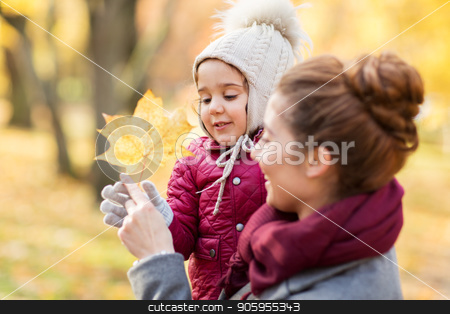 happy mother with little daughter at autumn park stock photo, family, season and people concept - happy mother and little daughter with maple leaf at autumn park by Syda Productions