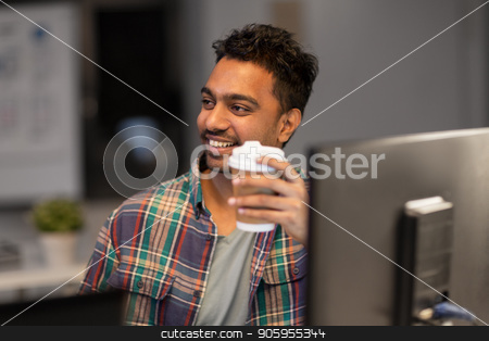 happy creative man drinking coffee at night office stock photo, deadline and people concept - smiling creative man working and drinking coffee at night office by Syda Productions