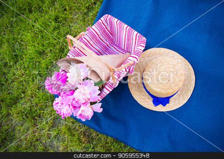 Bright summer picnic stock photo, A basket with beautiful flowers and a straw hat on a plaid by Sergiy Artsaba