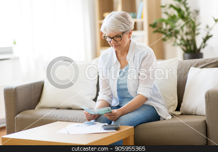 senior woman counting money at home stock photo, finances, savings, annuity insurance and people concept - senior woman with calculator and bills counting money at home by Syda Productions