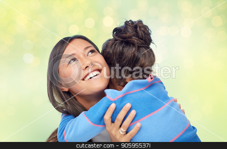 happy mother and daughter hugging over green stock photo, family, motherhood and people concept - happy mother and daughter hugging over green holidays lights background by Syda Productions