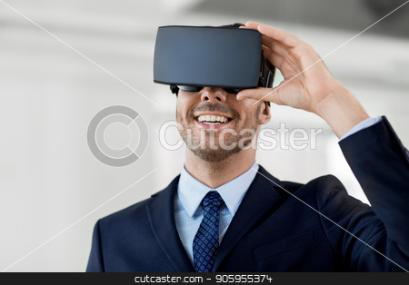 businessman with virtual reality headset at office stock photo, business, technology and augmented reality concept - smiling businessman with vr headset at office by Syda Productions