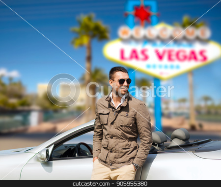 happy man near convertible car at las vegas stock photo, road trip, travel and people concept - happy man near convertible car over welcome to fabulous las vegas sign background by Syda Productions