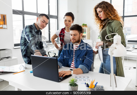 creative team working on user interface at office stock photo, business, technology and people concept - creative team or designers with laptop computer working on user interface at office by Syda Productions