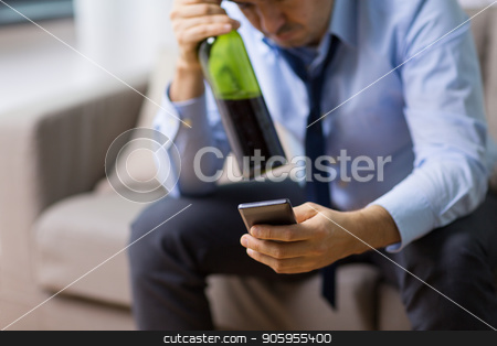 man with smartphone and bottle of alcohol at home stock photo, alcoholism, alcohol addiction and people concept - close up of drunk man with smartphone and bottle of wine at home by Syda Productions