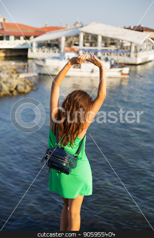 The girl is standing with her back on the pier. Summer, sun, sea, Bulgaria. stock photo, The girl is standing with her back on the pier. Summer, sun, sea, Bulgaria by Sergiy Artsaba