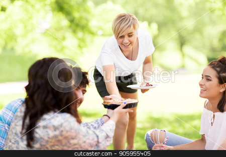 happy friends sharing pie at picnic in summer park stock photo, friendship, leisure and food concept - group of happy friends sharing pie at picnic in summer park by Syda Productions