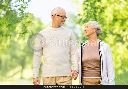 happy senior couple over green natural background stock photo, old age and people concept - happy senior couple holding hands over green natural background by Syda Productions