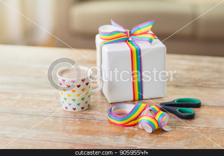 cacao, gift, gay awareness ribbon and scissors stock photo, homosexual and lgbt concept - cup of coffee or cacao drink with gift box, gay pride awareness ribbon and scissors on wooden table at home by Syda Productions