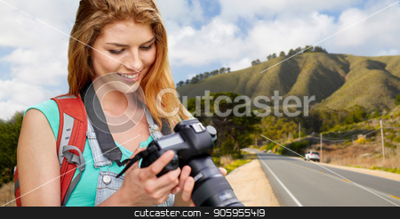 woman with backpack and camera over big sur hills stock photo, travel, tourism and photography concept - happy young woman with backpack and camera photographing over big sur hills of california background by Syda Productions