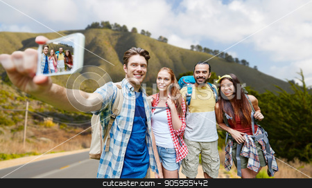 friends with backpack taking selfie by smartphone stock photo, technology, travel, tourism, hike and people concept - group of smiling friends with backpacks taking selfie by smartphone over big sur of california hills background by Syda Productions