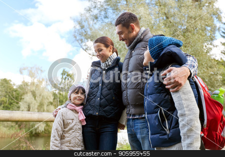 happy family with backpacks hiking stock photo, family, tourism and hiking concept - happy mother, father, son and daughter with backpacks in woods by Syda Productions