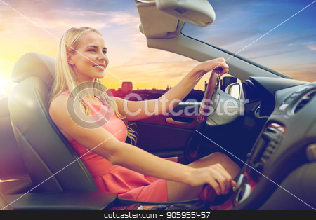 woman driving convertible car over city sunset stock photo, travel, road trip and people concept - happy young woman driving convertible car over city sunset background by Syda Productions