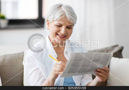 senior woman marking newspaper ad at home stock photo, age and people concept - senior woman marking newspaper ad at home by Syda Productions