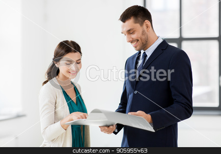 realtor with folder showing documents to customer stock photo, real estate business, sale and people concept - happy smiling realtor with folder showing documents to female customer at new office room by Syda Productions