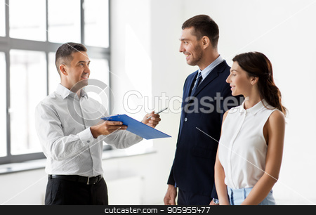 realtor showing contract document to customers stock photo, real estate business, sale and people concept - male realtor with clipboard and pen showing contract document to customers at new office room by Syda Productions
