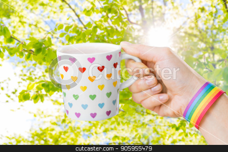 hand with cup of cacao and gay awareness wristband stock photo, homosexual and lgbt concept - female hand holding cup with rainbow colored heart pattern and gay pride awareness wristband over natural summer background by Syda Productions