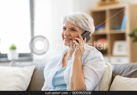 senior woman calling on smartphone at home stock photo, technology, communication and people concept - happy senior woman calling on smartphone at home by Syda Productions