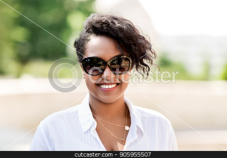 happy african american young woman in sunglasses stock photo, people, summer and eyewear - happy african american young woman in sunglasses outdoors by Syda Productions