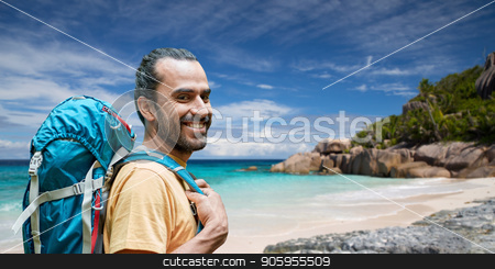 smiling man with backpack over seychelles stock photo, adventure, travel, tourism, hike and people concept - smiling man with backpack over background of seychelles island beach in indian ocean by Syda Productions